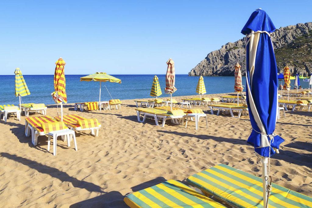 Tsambika empty sunbeds along sandy beach